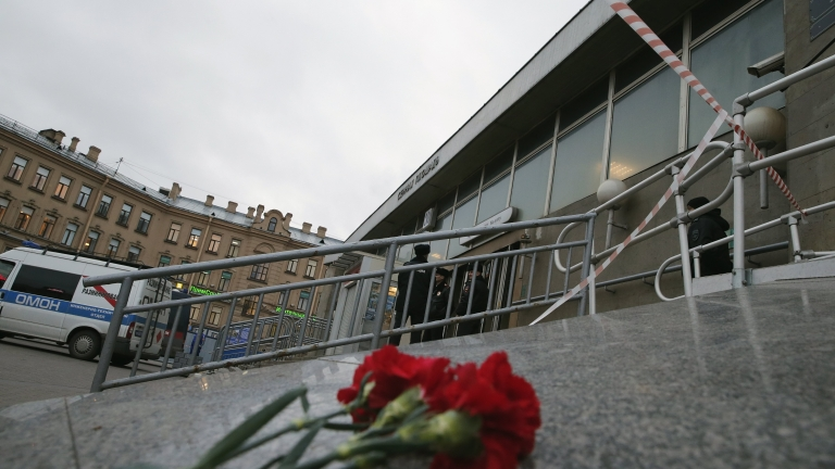 epa05886334 Flowers are placed outside Sennaya Ploshchad metro station after an explosion, in Saint Petersburg, Russia, 03 April 2017, as police officers secure the area. According to reports, at least 10 people were killed and dozens were injured in an explosion in the city's metro system. The cause of the blast was not immediately known. Russia's National Anti-Terrorist Committee said that the explosions hit a train between Sennaya Ploshchad and Tekhnologichesky Institut stations, media added. An anti-terror investigation is underway.  EPA/ANATOLY MALTSEV