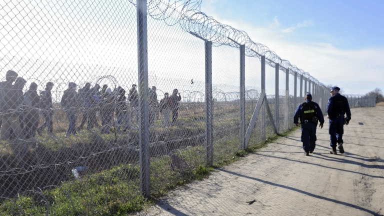 epa05175486 Patrolling Hungarian police officers watch migrants on Serbian territory, behind a Hungarian temporary protective fence at the border between Hungary and Serbia near Morahalom, Hungary, 22 February 2016. Some 501 migrants who crossed the border were detained by the Hungarian police over the weekend of 20 and 21 February, which is the highest number since autumn 2015.  EPA/ZOLTAN GERGELY KELEMEN HUNGARY OUT