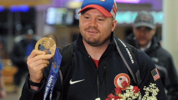 Team USA Olympic bobsled pilot Steve Holcomb arrives at Albany Airport with medals in hand Tuesday evening, Feb. 25, 2014, in Colonie, N.Y. Holcomb scored two bronze medals while piloting two and four-man bobsleds at the winter games in Sochi, Russia. Holcomb, and teammate Steve Langton, were the only 2 U.S. Olympians in Sochi to score individual medals in 2 events. (AP Photo/The Albany Times Union, Michael P. Farrell)  TROY, SCHENECTADY; SARATOGA SPRINGS; ALBANY OUT