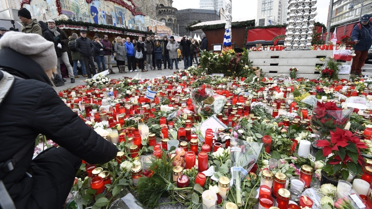 epa05685308 Visitors stand around a mass of candles and floral tributes placed at the recently re-opened Christmas Market on the Breitscheidplatz square in Berlin, Germany, 22 December 2016.An unknown assailant drove a truck into the crowded Christmas market in front of the Kaiser Wilhelm Memorial Church on 19 December evening killing at least twelve people and injuring around 50 more in what authorities said was a deliberate attack.  EPA/RAINER JENSEN
