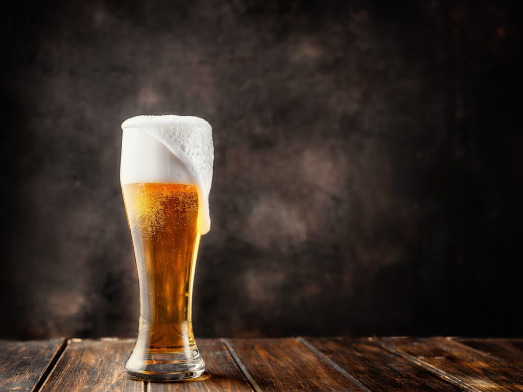 Glass of fresh and cold beer on dark background. Copy space.